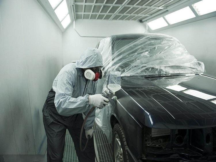 图为汽车喷漆房工人在工作